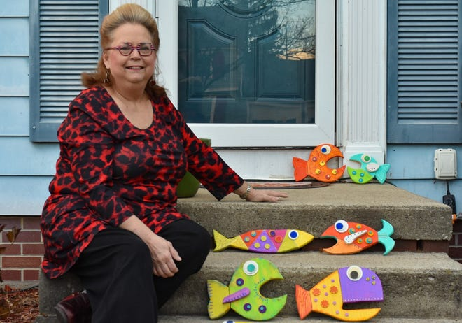 Rebecca Booth sits outside her Genoa home with a few of her handcrafted Funky Fish. Booth and other artists will be promoting the sale of their artwork this holiday season through the Greater Port Clinton Area Arts Council ChrisKindle Market.