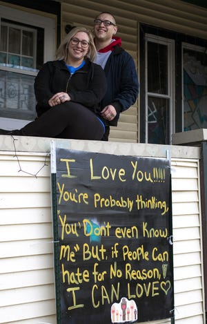 "Narvana Whitehead, shown with husband Drew, posted this ""I Love You"" sign outside her house at one of Wausau's busiest intersections. Jennifer Aniston recently shared a photo of their sign on her Instagram account."