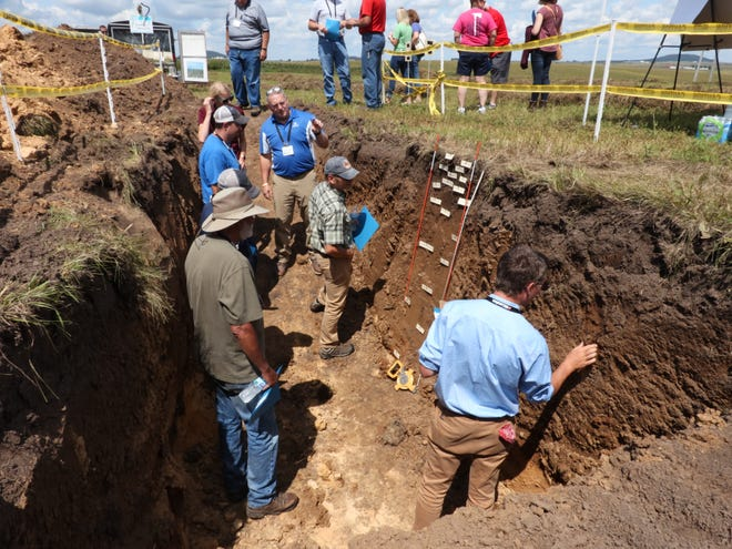 Participants at a field day with the Lafayette Ag Stewardship Alliance learn about how water penetrates soil pits, August 2019.