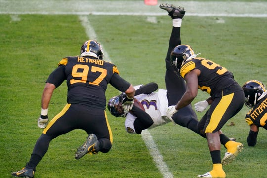 Baltimore Ravens quarterback Robert Griffin III (3) flies as he is tripped up as he scrambles past Pittsburgh Steelers defensive end Cameron Heyward (97) and inside linebacker Vince Williams (98) in the first half during an NFL football game, Wednesday, Dec 2, 2020, in Pittsburgh.