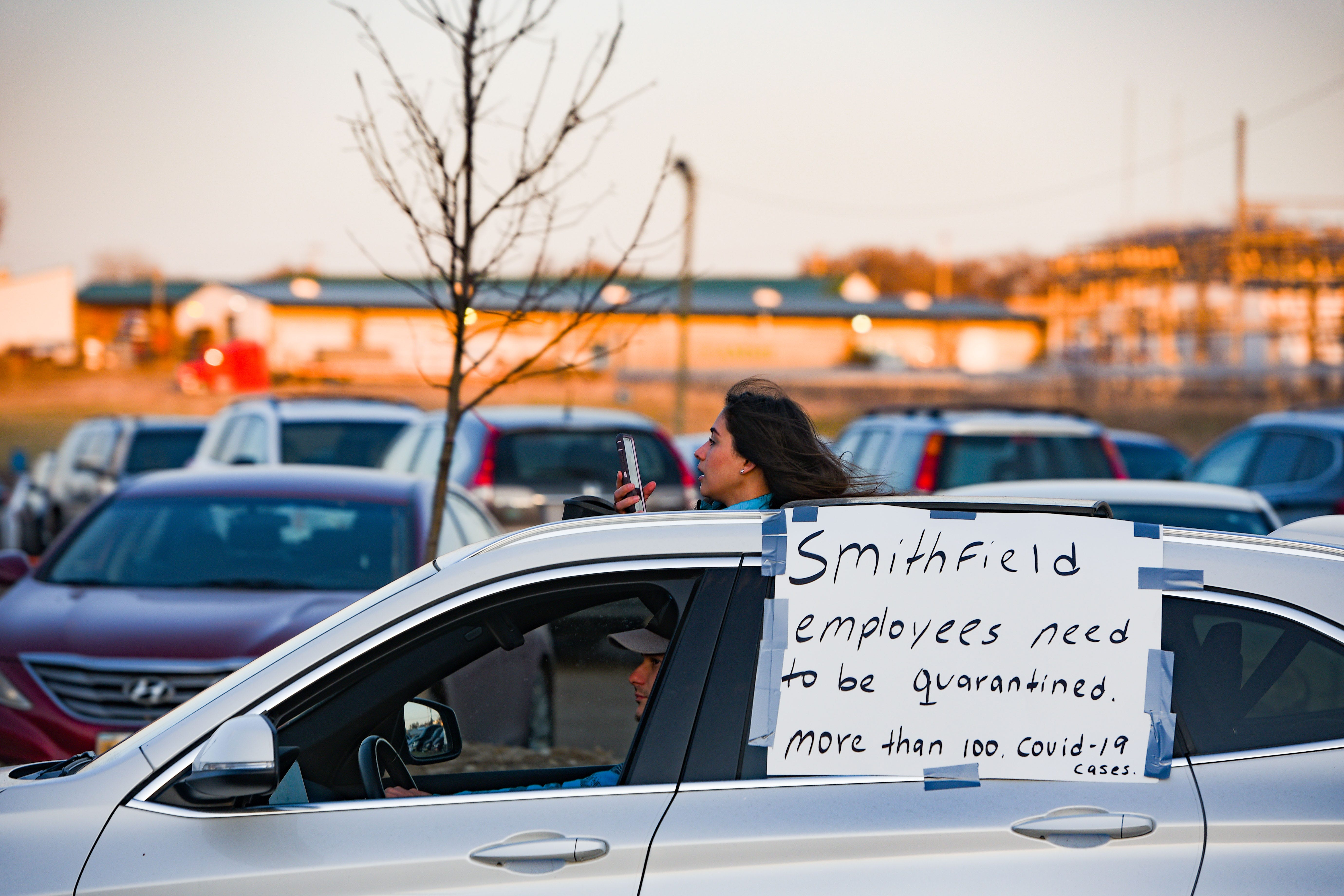 A protester records the demonstration on her phone out the sunroof of her car while driving in solidarity with Smithfield Food, Inc. employees after many workers complained of unsafe working conditions due to the COVID-19 outbreak on Thursday, April 9, in Sioux Falls, SD.