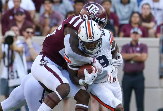 Auburn wide receiver Seth Williams (18) is tackled by Texas A&M defensive back Demani Richardson during their 2019 game at Kyle Field.