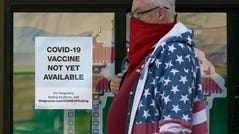 A pedestrian wearing a mask walks past a sign advising that COVID-19 vaccines are not available yet at a Walgreens in San Francisco on Wednesday.