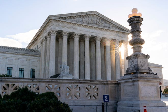 In this Nov. 10, 2020, file photo the sun rises behind the Supreme Court in Washington.