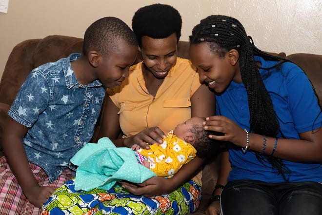 Esther Kinyana and her children Blessing, 8,  and Gloria, 13, look on at baby Gladys, who arrived in early October.