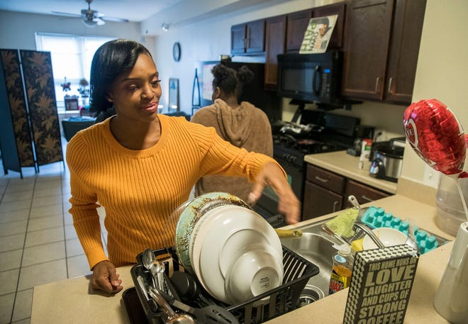 LaChantia Anderson, 39, does the dishes in her apartment. She is trying to get into coding and creating apps, and says 'I want a good job at a great company one day.' For the last four years, she has struggled with homelessness and being able to save up enough money to complete her course work.