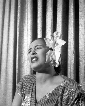 """Documentary """"Billie"""" peels back the layers of American blues singer Billie Holiday, shown singing with an orchid in her hair in the early 1950s."""