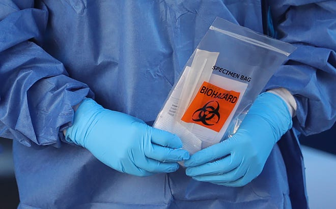A worker handles a specimen bag during a pop-up COVID-19 testing site Dec. 4 at the Summit County Public Health building in Akron.