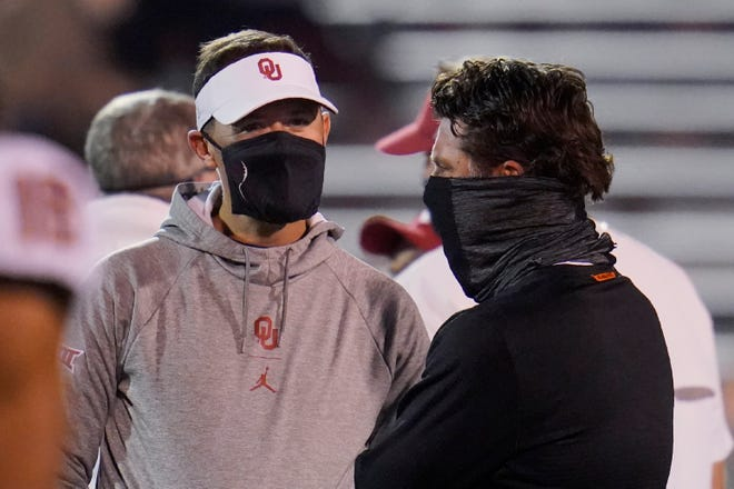 Oklahoma coach Lincoln Riley, left, talks with Oklahoma State coach Mike Gundy before an NCAA college football game in Norman, Okla., on Nov. 21.