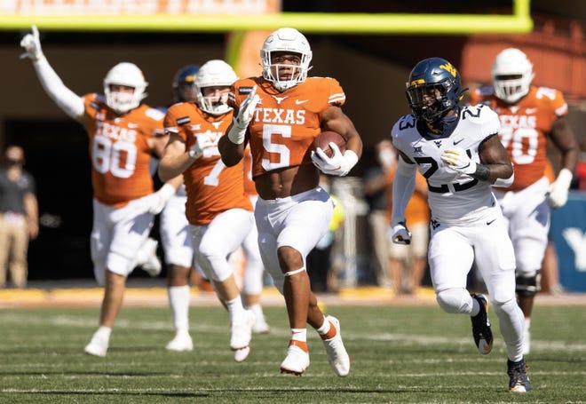Texas running back Bijan Robinson sprints past West Virginia safety Tykee Smith at Royal-Memorial Stadium on Nov. 7, 2020.