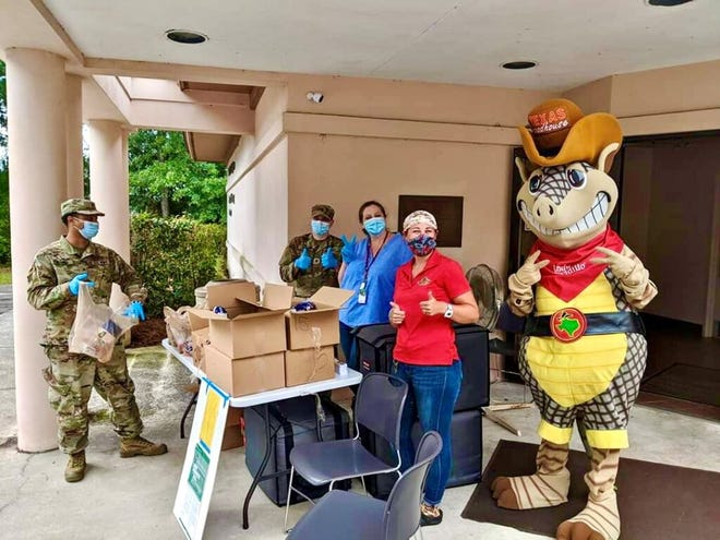 Cathy Driggers (center, in blue) works with volunteers and Georgia National Guard members to distribute food in June outside the Rincon Library in Rincon, Ga.