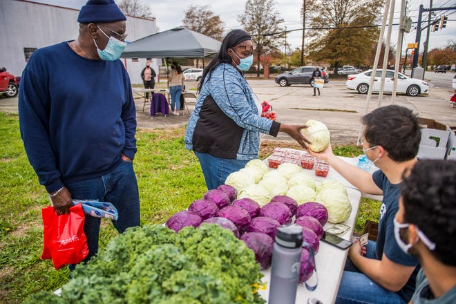 Andrea Asbury, middle, and her husband Benjamin Asbury, left, get some cabbage and tomatoes during the America Heart Association's farmers market in the Laney-Walker neighborhood in Augusta Friday afternoon. [MICHAEL HOLAHAN/THE AUGUSTA CHRONICLE]