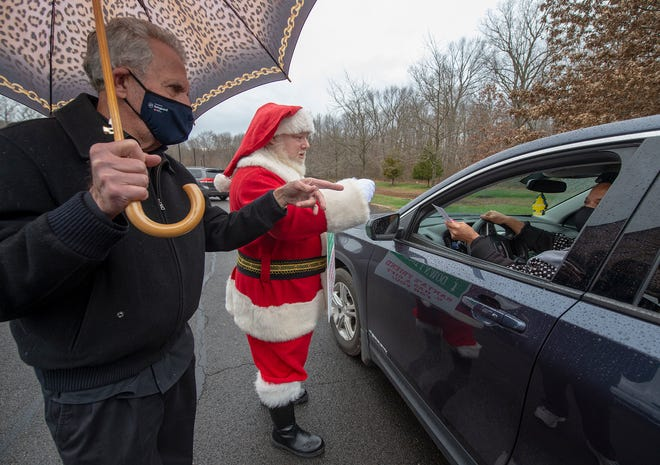 Philanthropist Gene Epstein, left, of Newtown, and Rob Piazza, of Bristol Borough, portraying Santa, give out $100 to Veronica Kelly, of Levittown, and others gathering at the Fresh Connect Food Distribution at the Gene and Marlene Epstein Campus of Bucks County Community College in Bristol Township, on Friday, Dec. 4, 2020.
