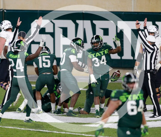 Michigan State players celebrate after scoring a touchdown on a fumbled Northwestern lateral as time expires during the fourth quarter of an NCAA college football game, Saturday, Nov. 28, 2020, in East Lansing, Mich.
