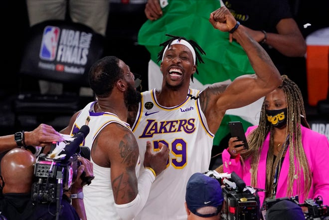 Los Angeles Lakers' LeBron James (23) and teammate Dwight Howard (39) celebrate after the Lakers defeated the Miami Heat in Game 6 of the NBA Finals on Oct. 11  in Lake Buena Vista, Fla.
