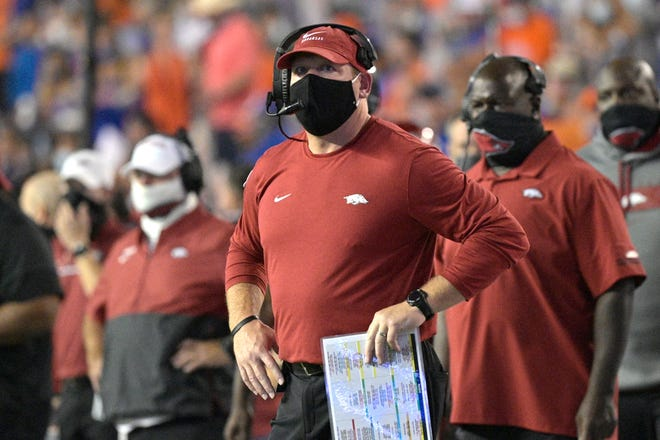 Arkansas defensive coordinator Barry Odom, center, watches a stadium video monitor after Florida scored a touchdown during a game Nov. 14 in Gainesville, Fla. Odom served as the Razorbacks' acting head coach for the game.