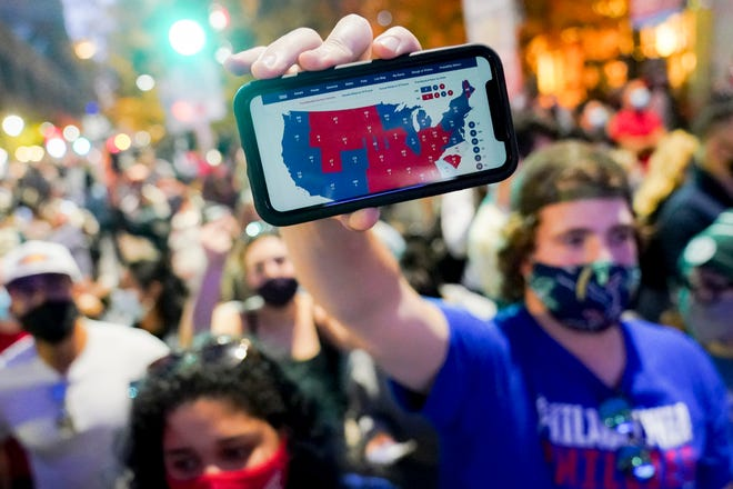 A supporter of President-elect Joe Biden holds up his mobile phone to display the electoral college map outside the Philadelphia Convention Center after the election was called Nov. 7.