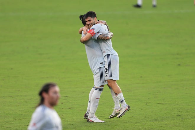 Forward Gustavo Bou lifts midfielder Carles Gil into the air after the New England Revolution defeated Orlando City on Sunday.
