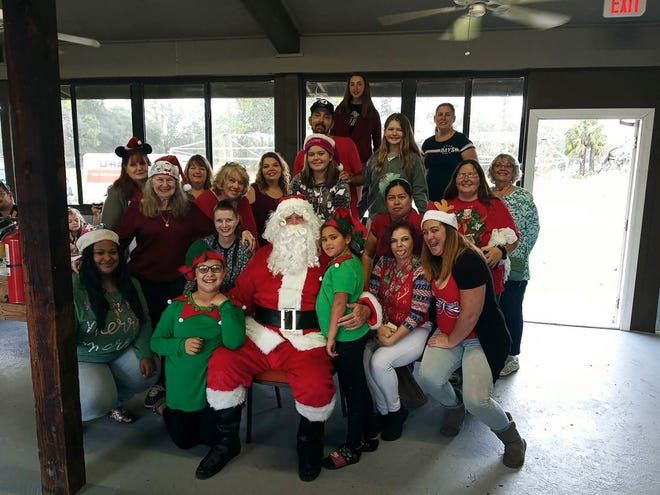 A group of volunteers from One To Another get a photo with Santa at their 2019 holiday event.