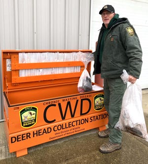 The Division of Wildlife's Erich Long removes deer head samples to be tested for Chronic Wasting Disease from the dropoff box at the Berlin Township Garage in Holmes County. Due to the COVID-19 pandemic this year, hunters used the self-serve station to drop off their mandatory deer head samples for deer harvested in five eastern Holmes County townships and two western Tuscarawas County townships during the deer-gun season.