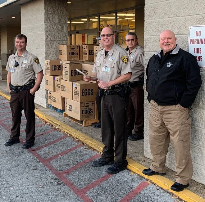 Deputies with the Maury County Sheriff's Department hand off Thanksgiving baskets.