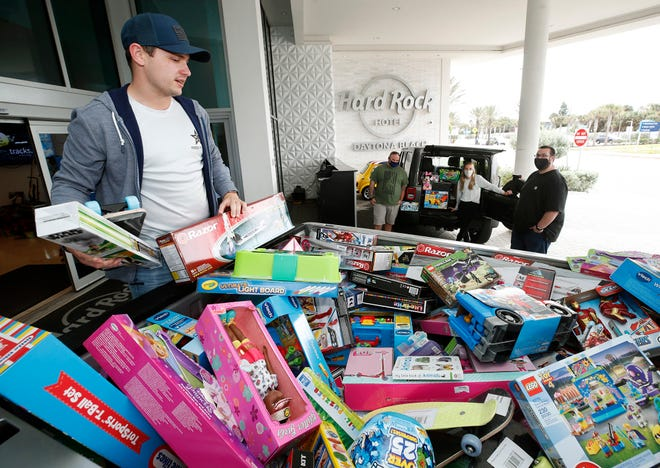 Country singer Reed Foley and friends arrive in trucks laden with toy donations on Friday at Hard Rock Hotel in Daytona Beach. The Ormond Beach singer is among the acts on the bill Saturday for the hotel's Rockin' Country Christmas event, a benefit for Toys For Tots. Admission to the show is one toy donation per person for the organization.