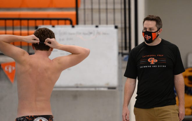 Cathedral Prep swim coach Mike Doyle talks with his swimmers before practice Friday at the Hallman Aquatics Center, Hagerty Family Events Center.