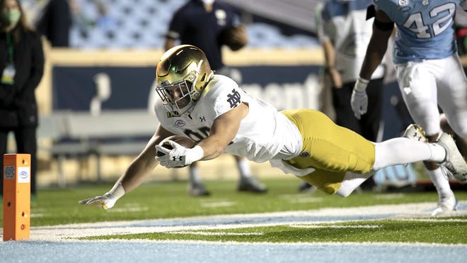 Notre Dame's George Takacs gets past North Carolina's Tyrone Hopper on a pass completion and dives toward the goal line during Nov. 27 game in Chapel Hill, North Carolina.
