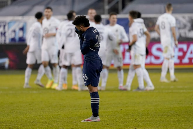 Sporting Kansas City defender Jaylin Lindsey (26) reacts on the field while Minnesota United players celebrate after a 3-0 upset in the MLS Western Conference semifinal Thursday night at Children's Mercy Park.