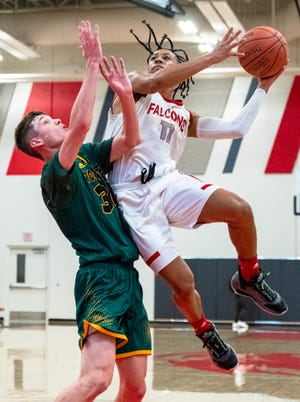 Van Horn guard Jaden Monday, right, draws contact from Columbia Rock Bridge defender Caden Sartain as he goes up for a shot in a game earlier this season. Monday, who is averaging 22.5 points, leads the Falcons into Friday's Class 5 state quarterfinal against No. 2-ranked Mexico.