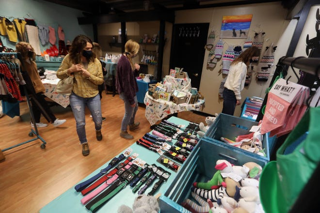 Shoppers browse the selection of merchandise Nov. 27 at Wiggle Butts, a new dog boutique in the loft of The Beancounter Coffeehouse and Drinkery at 212 Jefferson St. in downtown Burlington. The dog-centric boutique offers dog sweaters and coats, puppy tutus, treats, dog beds, leashes & collars, dog shirts for humans, dog decor and more.