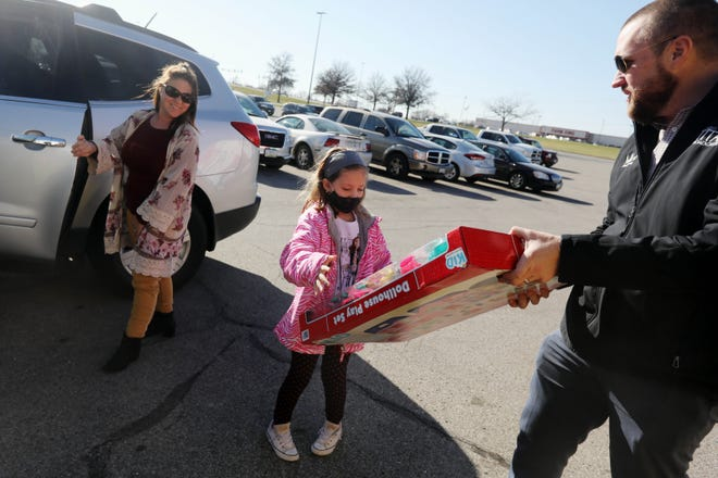 Payton Selby, 9, hands a doll house to LJ Pritchard Friday as her mother, Melissa, looks on during the Toys for Tots 2020 Semi of Love event hosted by the Marine Corp League at Westland Mall. Volunteers were collecting both toys and money to help area families have a joyful holiday season. The event continues from 7 a.m. to noon today.