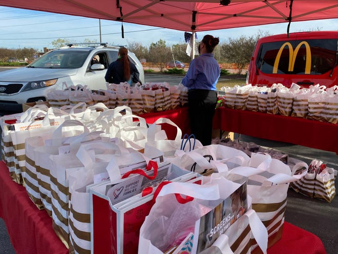 Team members and volunteers of Dixon Foods Group hand out care packages at a drive-thru event put on by Support Military Families in Jacksonville, Dec. 4.