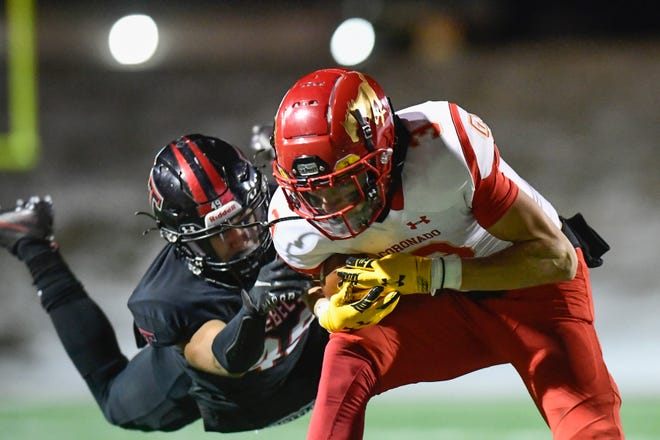 Amarillo Tascosa's Zaiquan Pinkard, left, tries to tackle Coronado receiver Cory Ferriera during the Mustangs' 35-33 victory Thursday in Amarillo. Coronado wrapped up an undefeated regular season and the District 2-5A Division I title by winning.