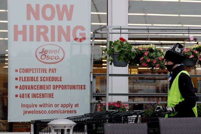 A man pushes carts as a hiring sign shows at a Jewel Osco grocery store in Deerfield, Ill., earlier this year.