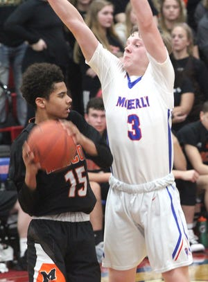 Zayne Montgomery of the Moberly Spartans raises his arms as he defends a Macon player during a game played in December of 2019 against the Tigers. The Moberly junior post player scored 15 points Thursday, but the Spartan boys lost 68-60 in overtime to Macon.