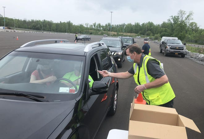 Interim Ontario County Administrator Brian Young, handing out face masks at a free distribution event in May, says the hiring of part-time nurses and interns will help address a recent spike in COVID-19 numbers.