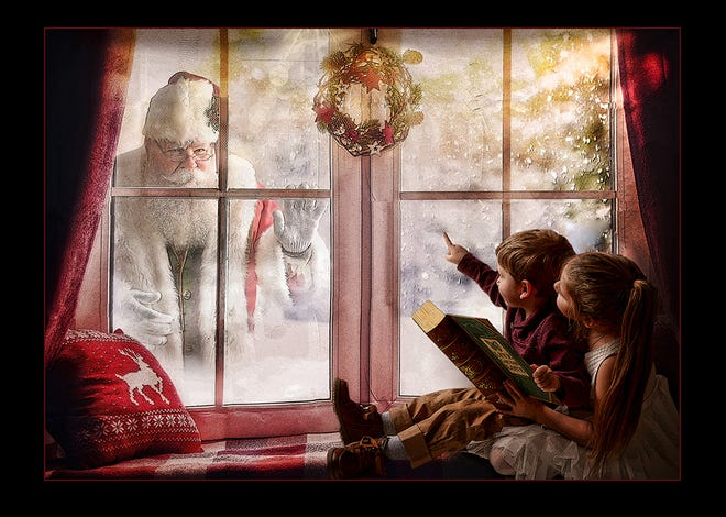 Santa peeks through a frosty window at cousins Lilly Langdon and Noah Spooner.