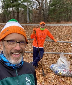 Peter Bakkala (near) and Dave Kittredge (far) collect cans and nip bottles on a recent run as part of the Highland City Striders Fireball Challenge.