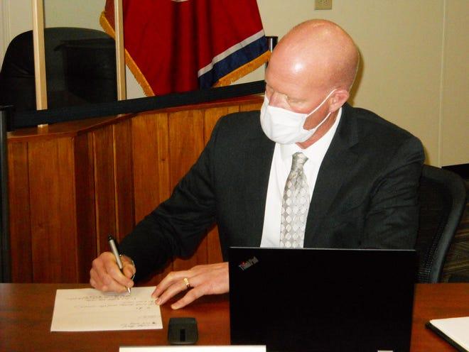 Oak Ridge Schools Superintendent Bruce Borchers shown writing while wearing a mask after an Oak Ridge Board of Education meeting.