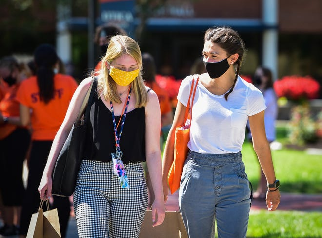 From left, Elizabeth Morgan and Anna Markwardt leave Addison Miller White Hall after attending orientation at Utica College last August.