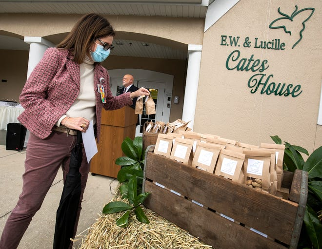 Dr. Mery Lossada, chief medical officer for Hospice of Marion County, grabs a bag of peanuts during the E.W. & Lucille Cates House dedication ceremony on Friday. E.W. Cates, a farmer and cattleman from Sparr, left $5 million to the organization in his will. It's one of the largest gifts received by a non-profit organization in Marion County