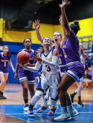 St. John's Katie Tagliaferro struggles to score against a tough Meadowbrook defense. The Mustangs topped the Saints, 57-23, Thursday night..
