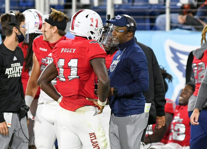 FAU quarterback Javion Posey and Coach Willie Taggart talk on the sideline during the Owls' 24-2 victory over UMass last month in Boca Raton.