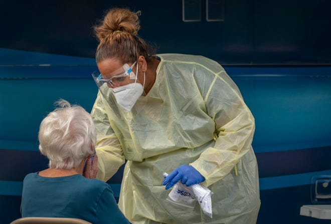 Healthcare worker Christine Chichester swabs a woman's nose for COVID-19 testing at a Healthcare District Mobile Testing unit set up outside the community center in Greenacres, Florida on December 3, 2020.