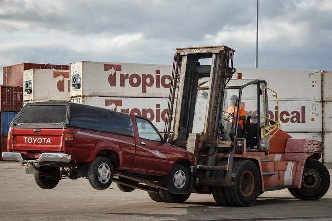 Used cars are loaded onto ships for delivery to Haiti at the Port of Palm Beach in December.