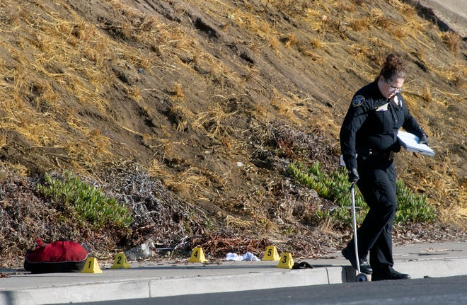 A Stockton police evidence technician measures the scene of a homicide near Monte Diablo Avenue and Interstate 5 in Stockton on Friday.