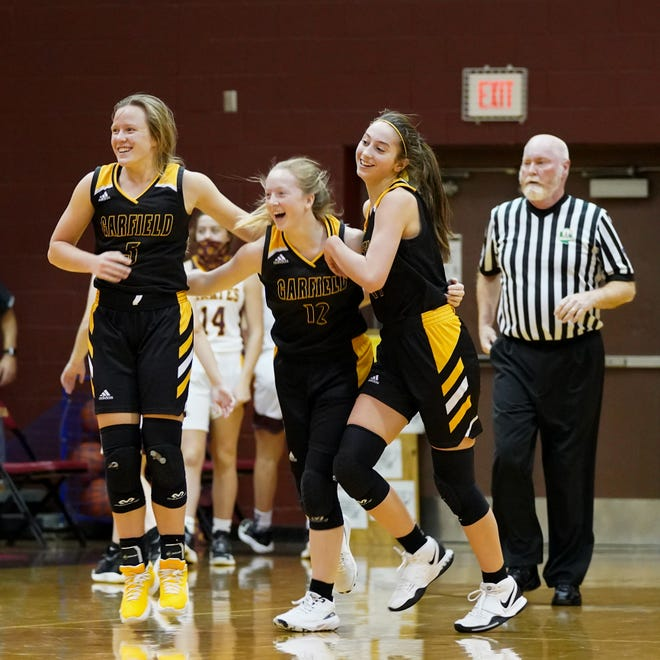 From left, Grace Mills, Caitlin Lutz and Madeline Shirkey celebrate after Garfield's win over Southeast Dec. 3.