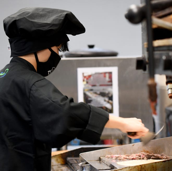 Jackson High School junior Owen Debski works the grill as students in the Culinary Arts Program at Jackson High School prepare takeout meals in the Bear's Den Cafe kitchen last week.