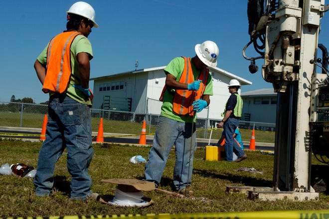 Workers extract water samples, at Bayshore High School, in Bradenton, Fla., in 2007.